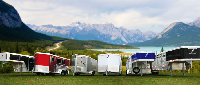 Featherlite lineup of various horse trailers in front of mountain range