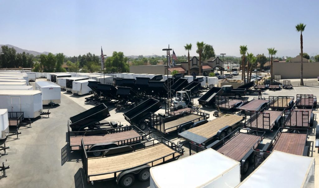 Parking lot full of dump trailers, utility trailers, and enclosed cargo trailers